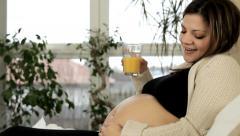 Pretty pregnant woman drinking orange juice Stock Footage