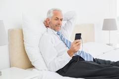 Businessman listening music with his phone in bed Stock Photos