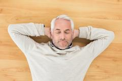 Stock Photo of Overhead view of a man sleeping on parquet floor