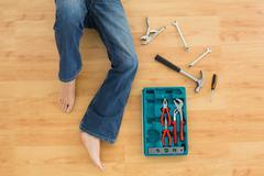 Stock Photo of Man lying with several tools on parquet floor