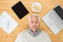 Stock Photo of Mature man sleeping with electronics and biscuits on parquet floor