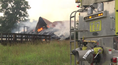 Firefighters firetruck at barn burning Stock Footage