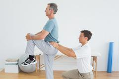 Therapist massaging mans lower back in gym hospital Stock Photos