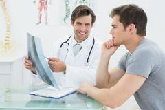 Smiling doctor explaining spine x-ray to patient - stock photo