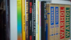 Going past many art and fashion books on a bookcase - stock footage