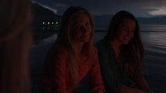 Three Teenage Girls Talking On A Beach At Night Stock Footage