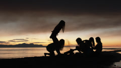 Group of Five Teenage Girls Lighting Sparklers At A Campfire On The Beach Stock Footage