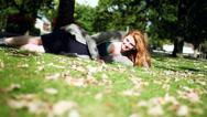 Stock Video Footage of Cheerful redhead relaxing lying on green lawn