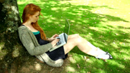 Stock Video Footage of Gorgeous redhead typing on notebook leaning against tree