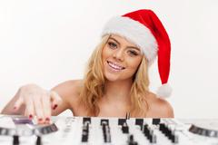 young brunette woman in christmas wear with dj equipment - stock photo
