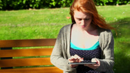 Stock Video Footage of Peaceful woman working with her tablet sitting on bench