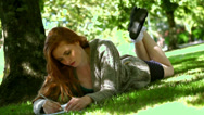 Stock Video Footage of Young redhead lying on lawn while doing assignments