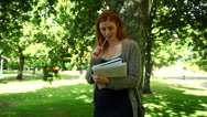 Stock Video Footage of Lovely thinking redhead doing assignments standing in park