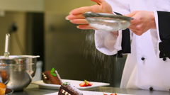 Chef sieving icing sugar over a dessert Stock Footage