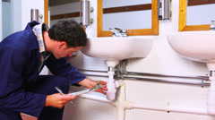 Handsome plumber looking at sink holding clipboard Stock Footage