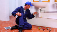 Stock Video Footage of Handsome plumber fixing sink and checking tablet pc