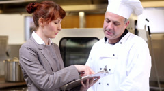 Restaurant manager speaking with head chef Stock Footage