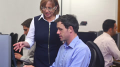 Teacher helping mature student in computer class Stock Footage