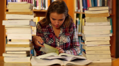 Attentive student studying in the library surrounded by books - stock footage