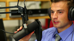 Handsome student reading the news on radio in the studio Stock Footage