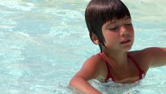 kid rubbing eyes in a swimming pool - stock footage