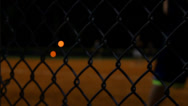 Stock Video Footage of Blurred softball players through a fence