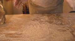 Hands dropping ball of dough onto floury surface - stock footage