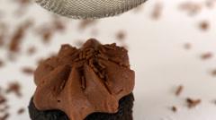 Icing sugar being sieved on chocolate cupcake - stock footage