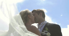 Bride and groom kissing each other outside on a sunny day Stock Footage