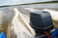 outboard motor boat on the river - stock photo