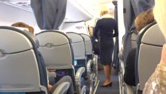 Flight attendant in airplane Stock Footage