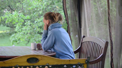 Lady drinking hot morning coffee in garden bower Stock Footage