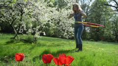Pretty woman turn hula hoop ring on waist in spring garden Stock Footage