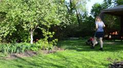 Young woman cut lawn near garden bower Stock Footage