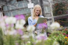 A woman working with digital tablet flower nursery Stock Photos
