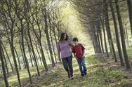 Stock Photo of A woman and child walking down an avenue of trees