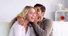 Man whispering a secret to his girlfriend on the couch Stock Footage
