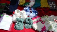 Hand take homemade wool knitted warm cozy baby shoes sold market Stock Footage