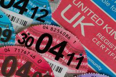 Car registration certificate with car tax discs Stock Photos