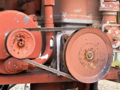 vintage belt driven engine gear wheels - stock photo