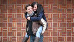 Man giving woman piggy back ride Stock Footage
