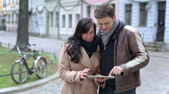 Couple using tablet computer in city Stock Footage