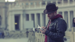 Tourist reading a guide near the Basilica of St. Peter Stock Footage