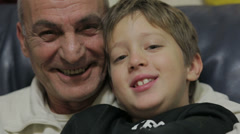 grandfather and grandson laughing and looking at the camera -  old man and child - stock footage