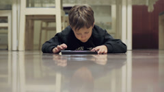 Child surfing in internet with a tablet lying on the floor Stock Footage