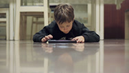 Stock Video Footage of child surfing in internet with a tablet lying on the floor