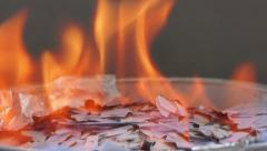 Burning pieces of paper in a plate Stock Footage