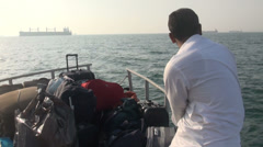 Iranian man looks out over Persian Gulf on a moving ferry Stock Footage