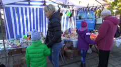 Parents buy sweet candies for kids children in city street fair Stock Footage