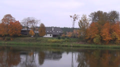 Autumn scenery along the river shore  autumn trees and houses Stock Footage